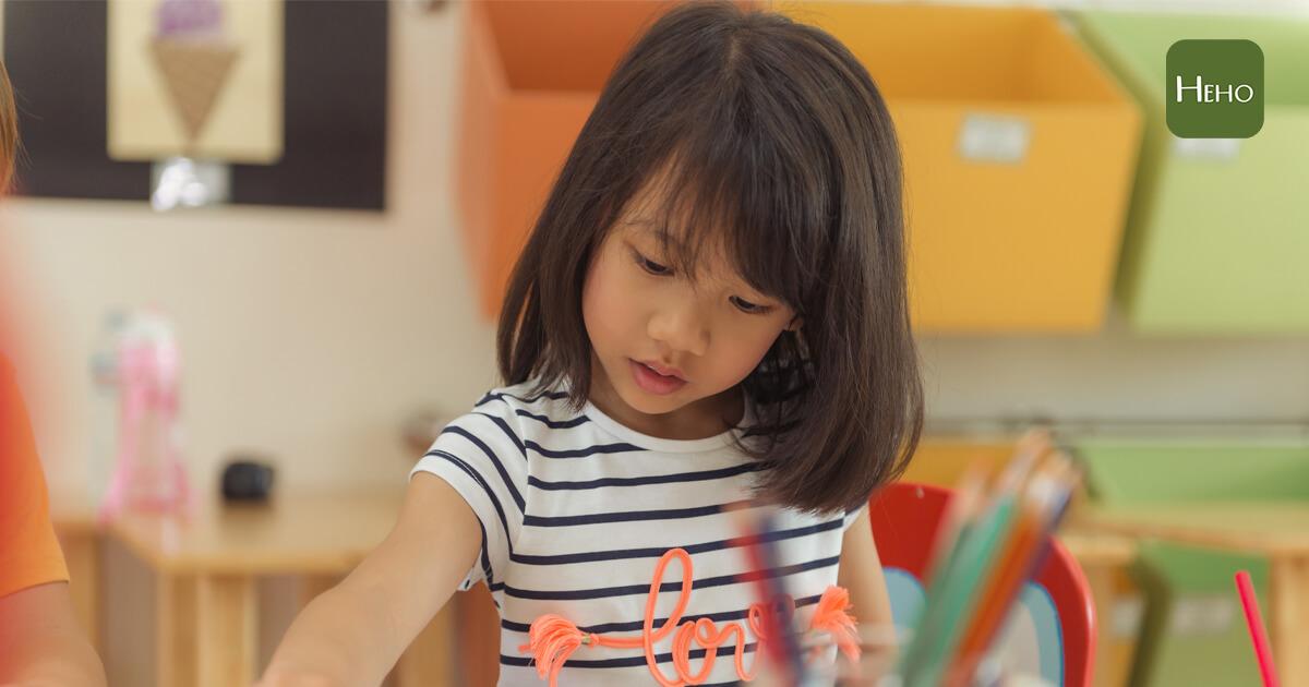Girl drawing color pencils in kindergarten classroom, preschool